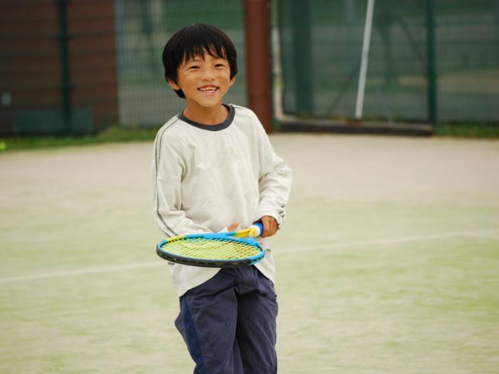 テニスを楽しむ小学生