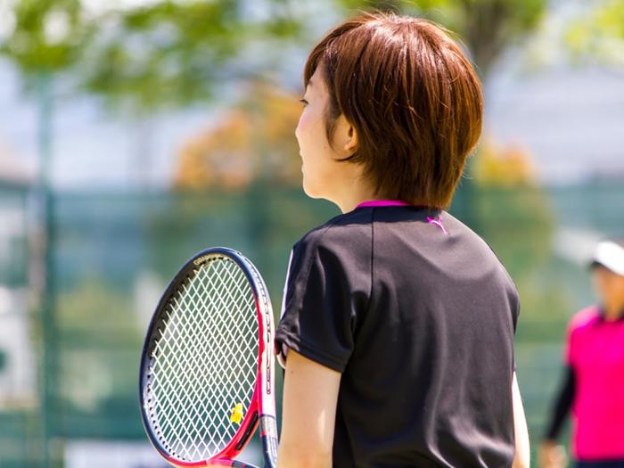 テニスをする女性の後ろ姿