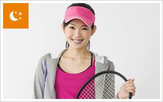 笑顔でテニスラケットを持つ女性